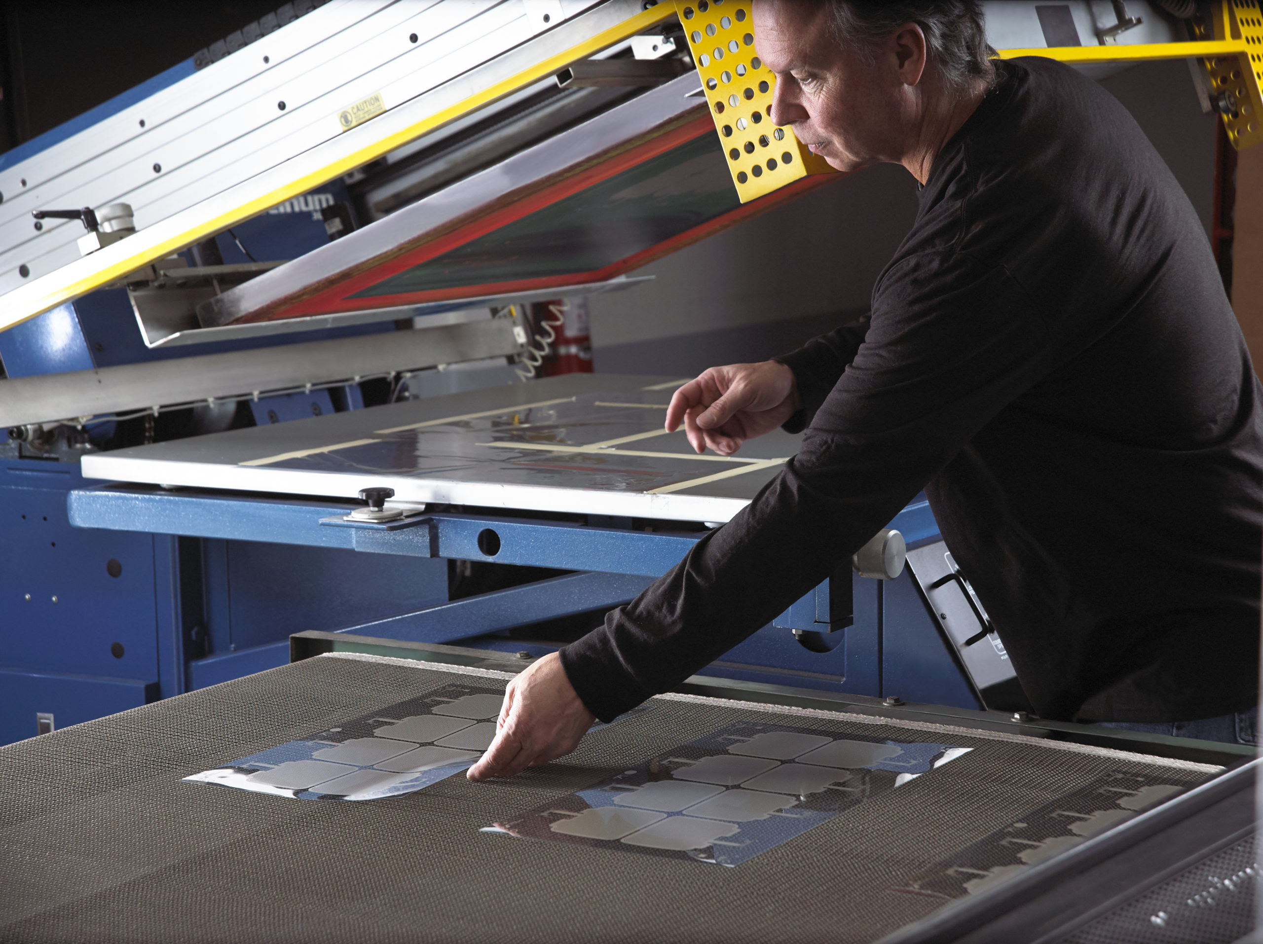 Technician placing membrane printed from silkscreen machinery on dryer belt