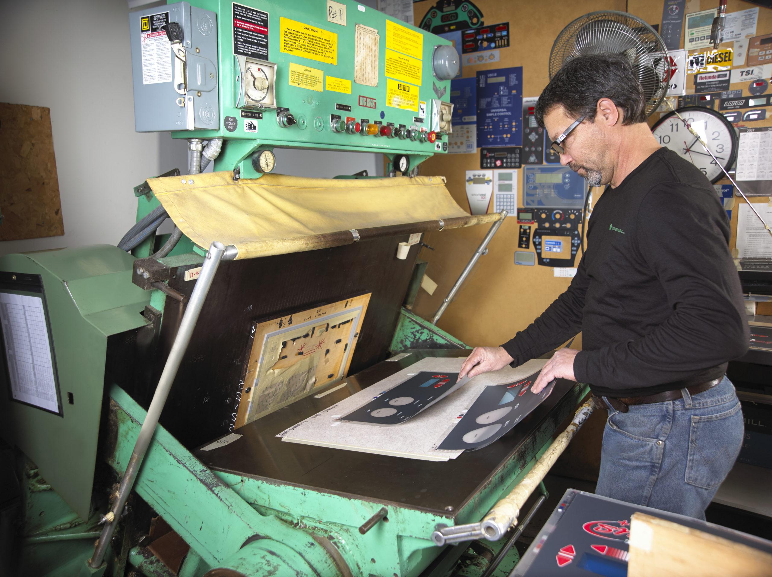 Technician operating die cutting machine